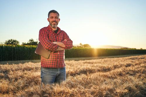 Landwirt mit Karohemd und Tablet steht im Getreidefeld im Sonnenuntergang